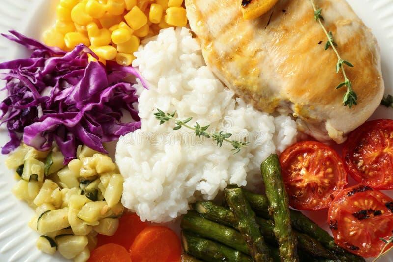 Kokade ris med grönsaker och kött på plattan, closeup arkivfoto