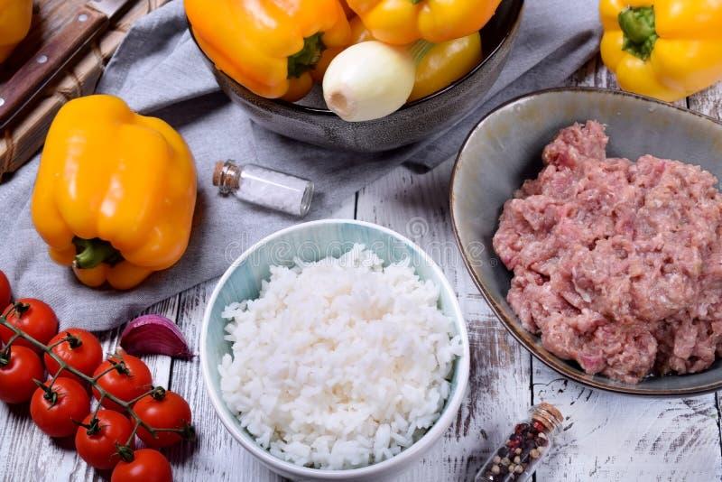 Kokade ris, rått griskött och nötkött finhackar och gula spanska peppar arkivfoton