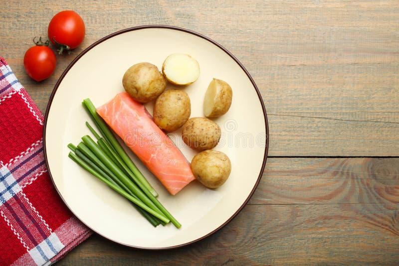 Kokade unga potatisar med den röda fisken, lökar och körsbärsröda tomater royaltyfri foto