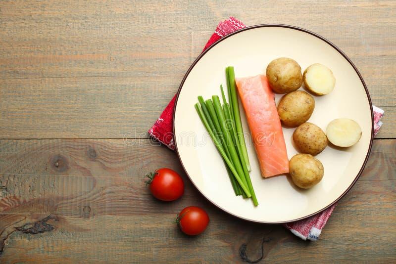 Kokade unga potatisar med den röda fisken, lökar och körsbärsröda tomater royaltyfri fotografi