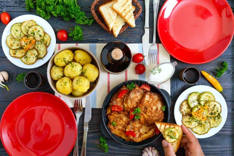 Kokade unga potatisar, stekte zucchiniskivor, schnitzlar på en trätabell Top besk?dar Tjänad som tabell för familjmatställen, lun arkivbilder