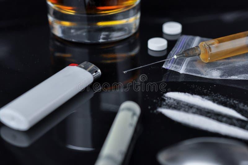 Kokain, preventivpillerar, alkohol och heroin i injektionsspruta arkivfoto