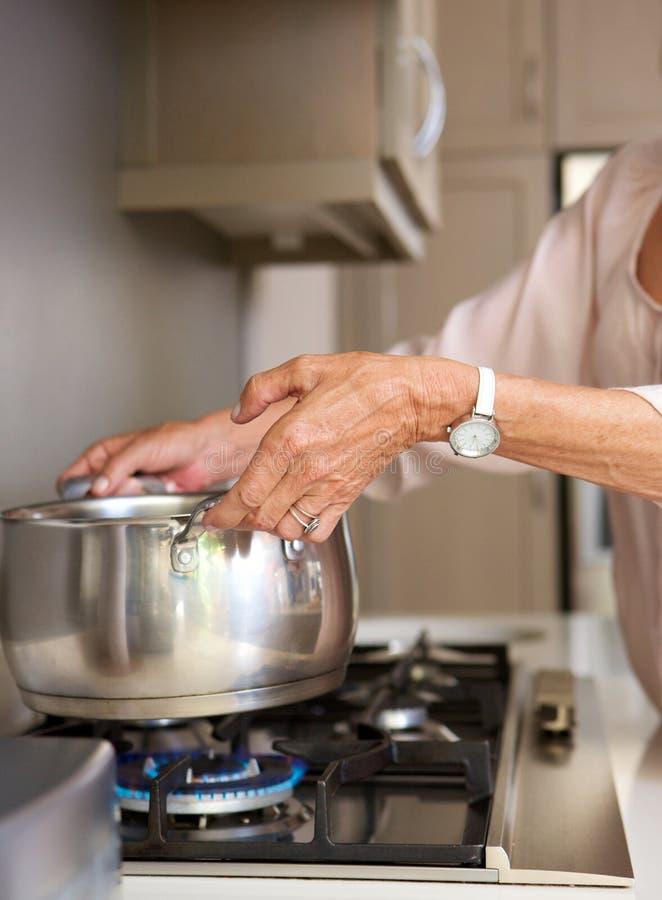 Kokande vatten för äldre kvinna i kruka på ugnöverkant royaltyfria foton