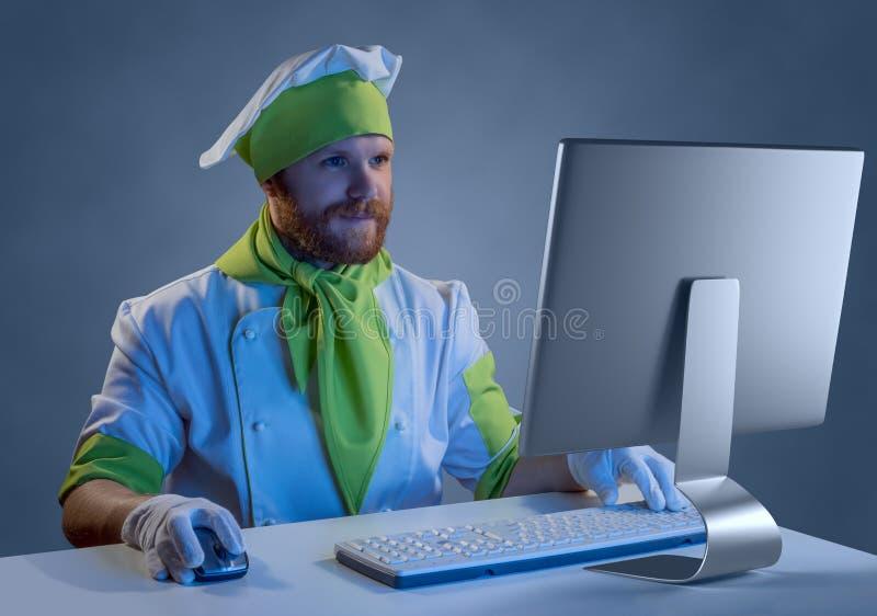 Kokchef-kok die bij een computer met toetsenbord en muis werken stock afbeeldingen