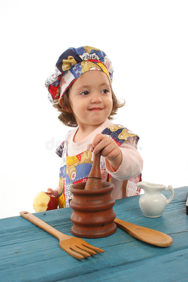 Koken van het meisje gekleed als chef-kok stock afbeeldingen