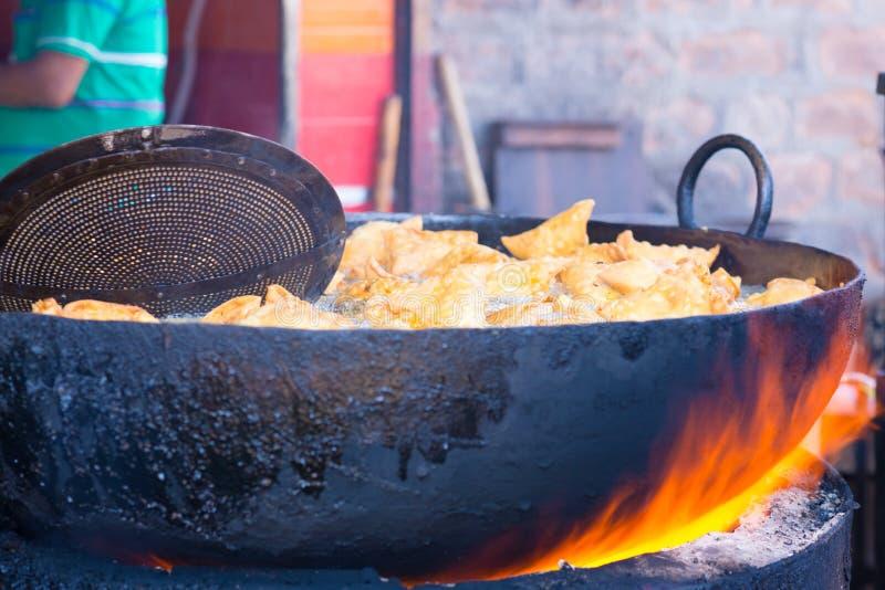 Kokend en friturend in fatiscent grote pan of wok, de box van het straatvoedsel in India, troep het ongezonde eten Brand die uit  stock foto's
