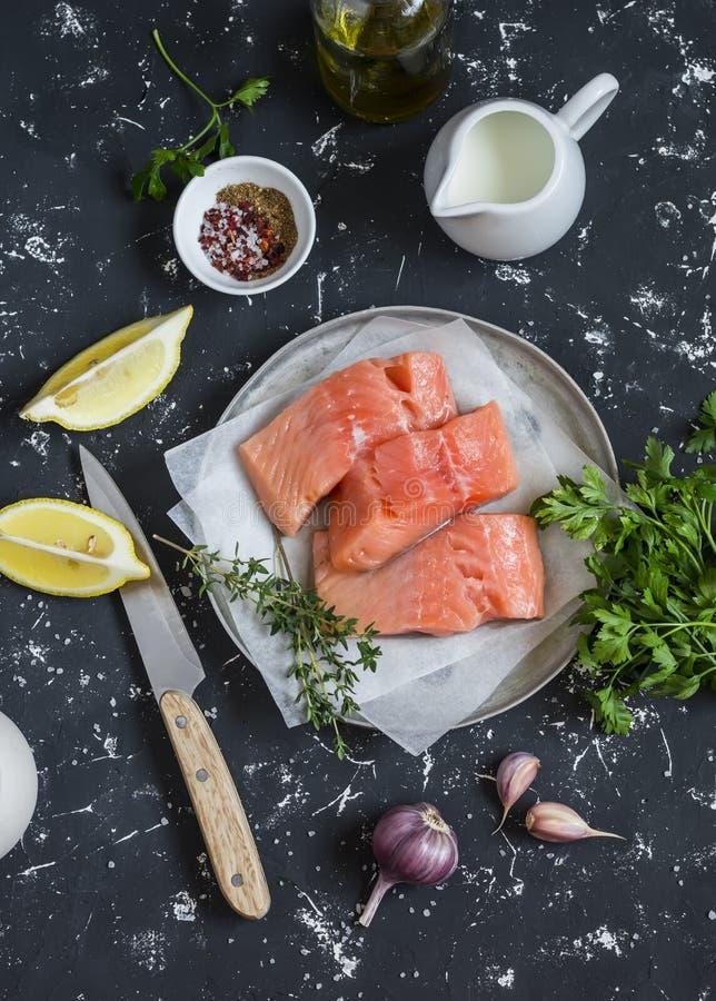Kokend gezonde lunch - ruwe zalm, citroen, olijfolie, kruiden en kruiden op een donkere achtergrond stock foto's