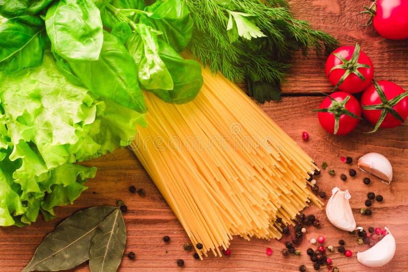 Kokend Italiaanse deegwarenspaghetti met kersentomaten, vers groen basilicum, salade en kruiden - hoogste mening over houten acht royalty-vrije stock afbeeldingen