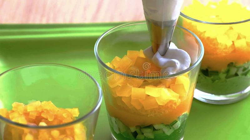 Kokend roomdessert in een glas, gelaagd met lagen vruchten en noten de kok spreidt de lagen uit royalty-vrije stock afbeeldingen