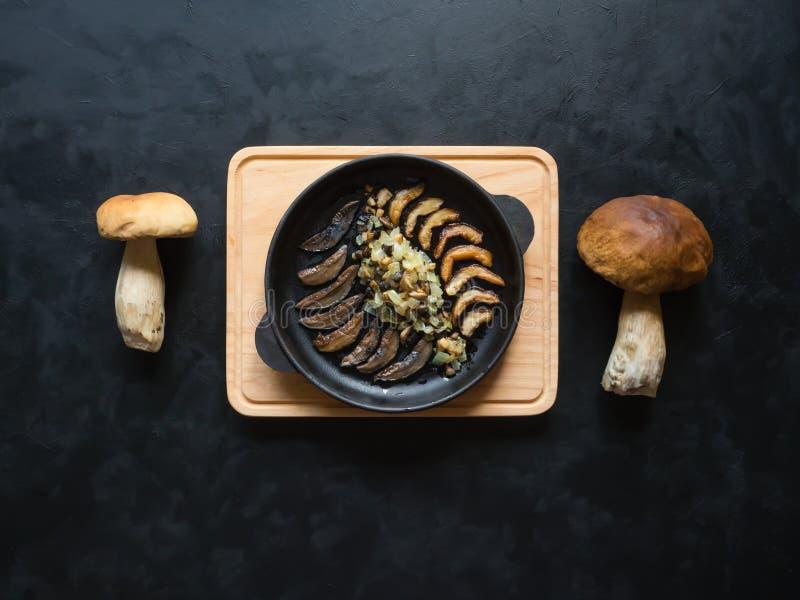 Kokend stuiverbroodje Gebraden eekhoorntjesbroden in een ijzerpan op de zwarte lijst Hoogste mening royalty-vrije stock afbeelding