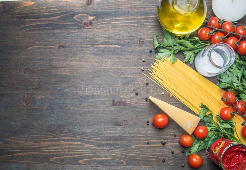 Kokend vegetarische deegwaren met kersentomaten, peterselie, ui en knoflook, boter, tomatenpuree en kaas, op rustieke houten rug stock afbeelding