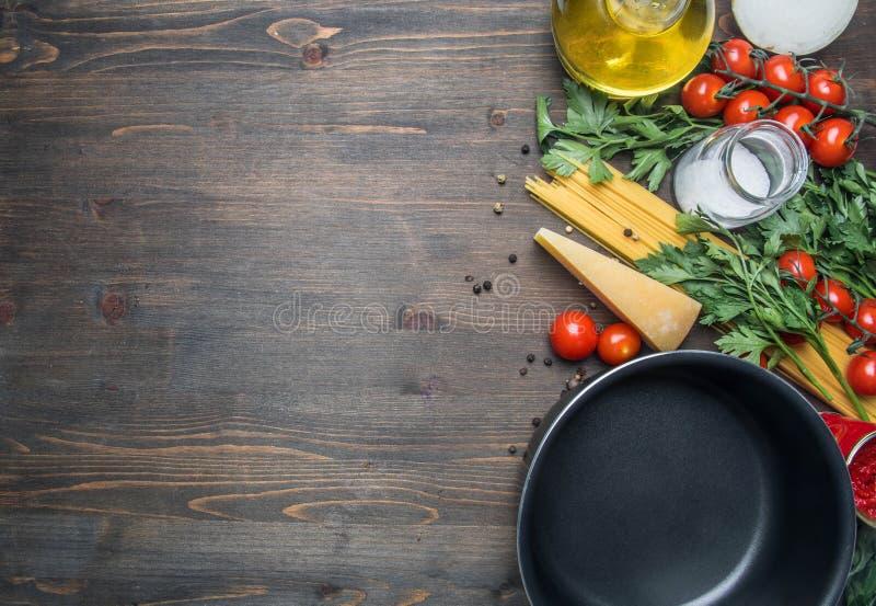 Kokend vegetarische deegwaren met kersentomaten, peterselie, ui en knoflook, boter, tomatenpureekaas, op een rustieke houten rug royalty-vrije stock foto