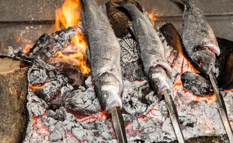 Kokend vissen die over heet steenkolenvuur worden geroosterd royalty-vrije stock afbeeldingen