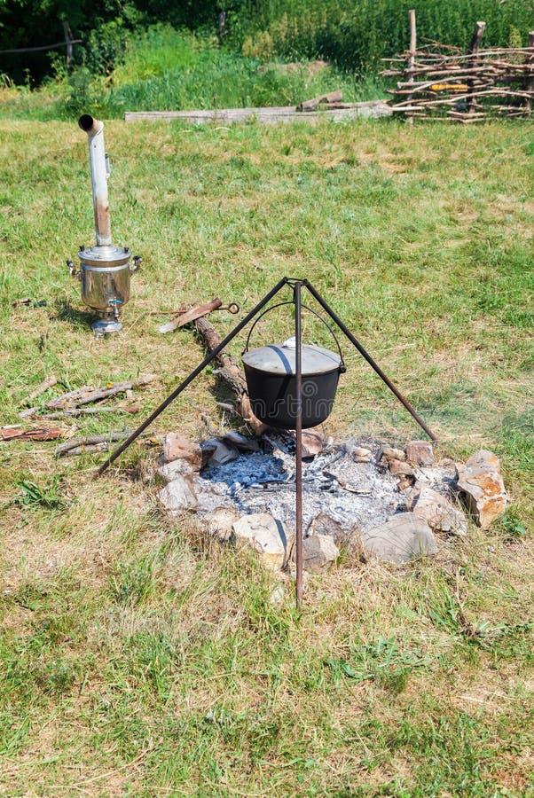 Kokend voedsel op een kampvuur in openlucht in de zomerdag stock afbeelding