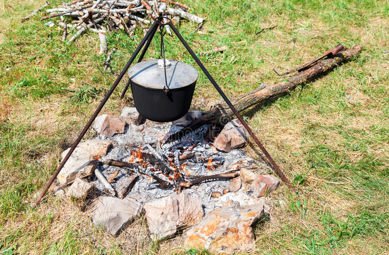 Kokend voedsel over een open brand bij het kampeerterrein in de zomer royalty-vrije stock afbeeldingen