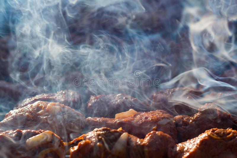 Kokende barbecue op de grill met rook Vlees bij de grill Ochtendbbq Kok vers gemarineerd vlees met uien Gemarineerde grill royalty-vrije stock afbeeldingen