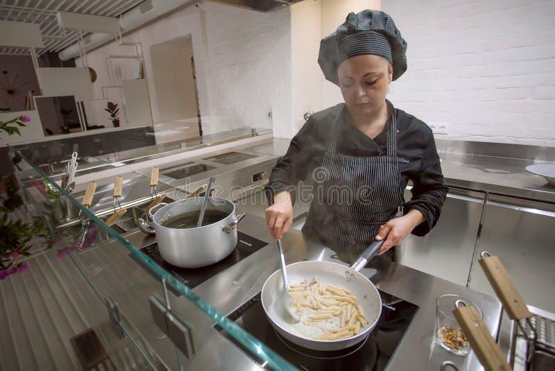 Kokende chef-kok die Italiaanse voedseldeegwaren of spaghetti maken bij open keuken binnen modern restaurant royalty-vrije stock foto