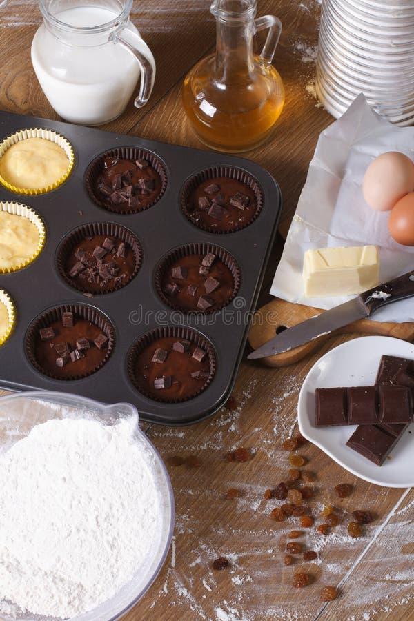 Kokende chocolade en vanille cupcakes close-upverticaal royalty-vrije stock fotografie