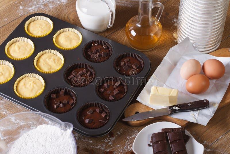 Kokende chocolade en vanille cupcakes hoogste horizontale mening stock foto's