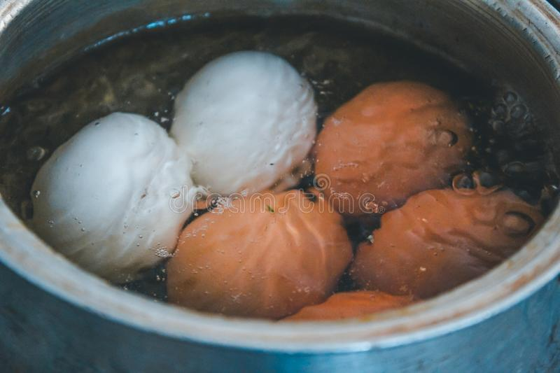 Kokende eieren in water stock fotografie