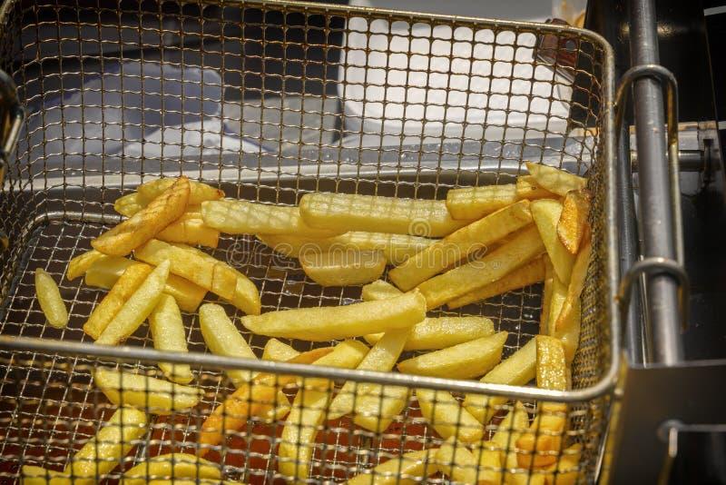 Kokende Frieten in een hete braadpan in hete olie royalty-vrije stock foto