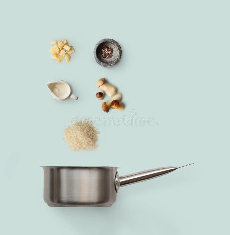 Kokende ingrediënten, Italiaanse risotto met wilde die paddestoelen op blauw worden geïsoleerd stock afbeelding