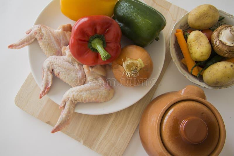 Kokende ingrediënten: kippenvleugels en plantaardige hutspot stock afbeelding