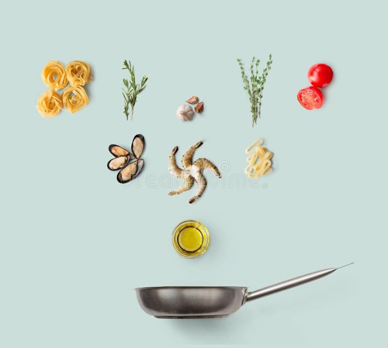 Kokende ingrediënten voor Italiaans die voedsel, zeevruchtendeegwaren, op blauw worden geïsoleerd stock foto's