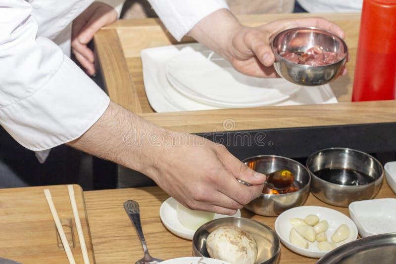 Kokende Koreaanse schotels, ingrediënten voor maaltijd kokkoks in keuken stock foto's