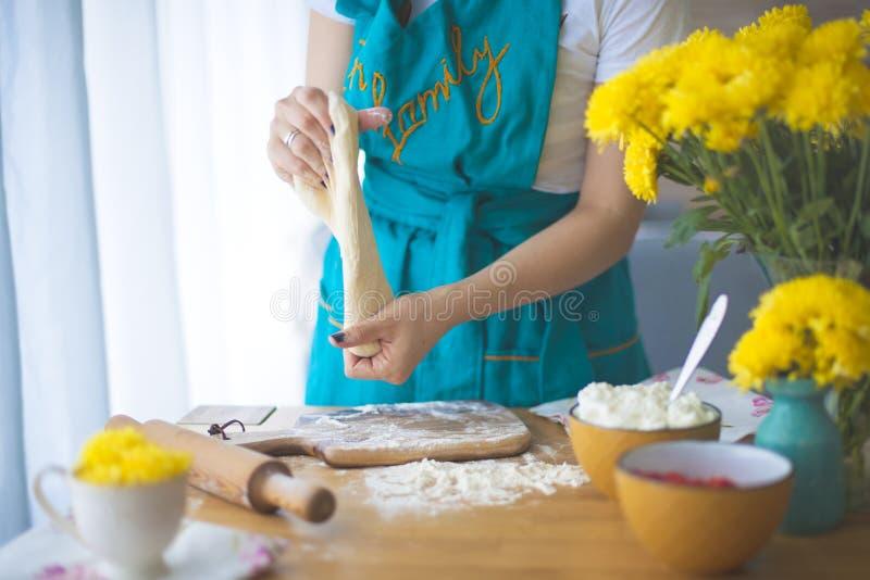 Kokende pastei Comfortabel huis De vrouw werkt met de test, op de lijst ligt een deegrol en een bloem stock afbeelding