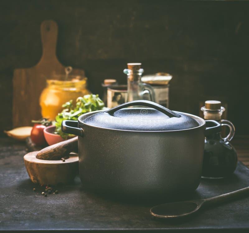 Kokende pot die zich op rustieke keukenlijst bevinden met organische ingrediënten, kruiden en het kruiden Gietijzer kokende pan e royalty-vrije stock afbeeldingen