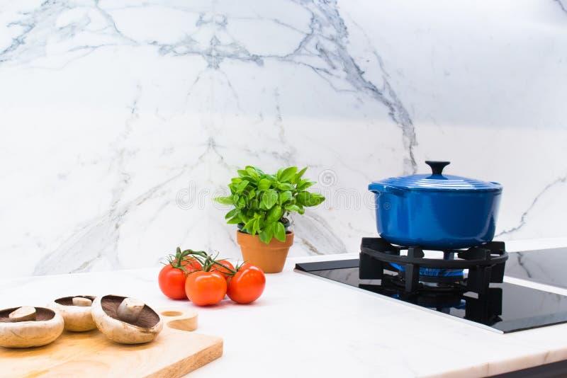 Kokende pot en ingrediënten op marmeren keukenbank stock foto