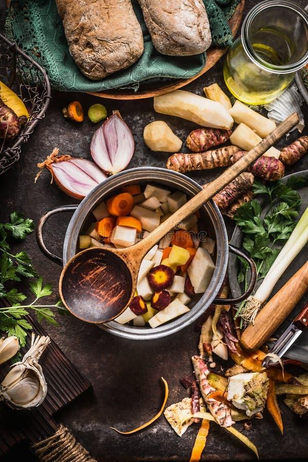Kokende pot met houten lepel en groenten op de rustieke achtergrond van de keukenlijst Eigengemaakt gezond voedsel en het eten stock afbeeldingen