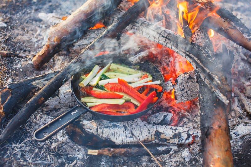 Kokende schotels van rode groene paprika's en komkommers in een pan op een brand stock foto's