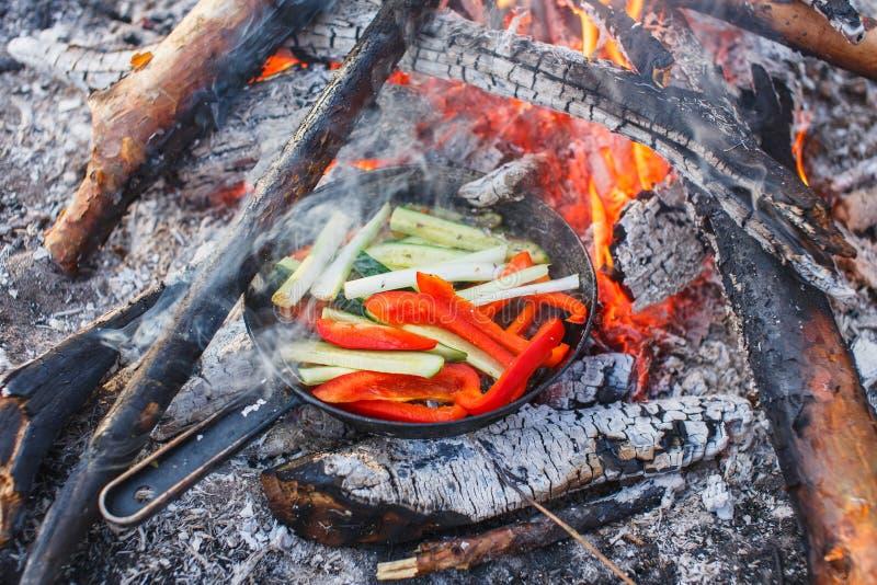 Kokende schotels van rode groene paprika's en komkommers in een pan op een brand royalty-vrije stock foto