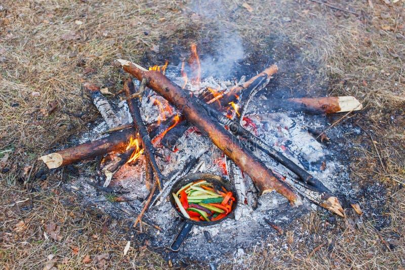 Kokende schotels van rode groene paprika's en komkommers in een pan op een brand stock afbeeldingen