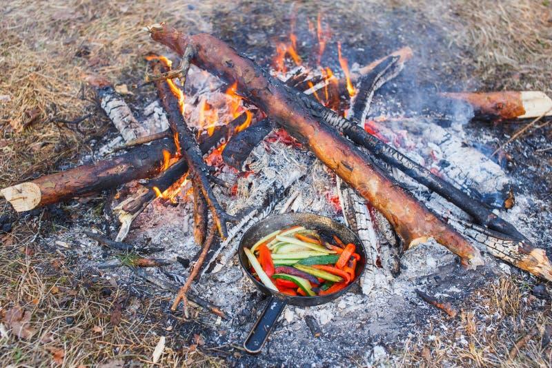 Kokende schotels van rode groene paprika's en komkommers in een pan op een brand royalty-vrije stock foto's