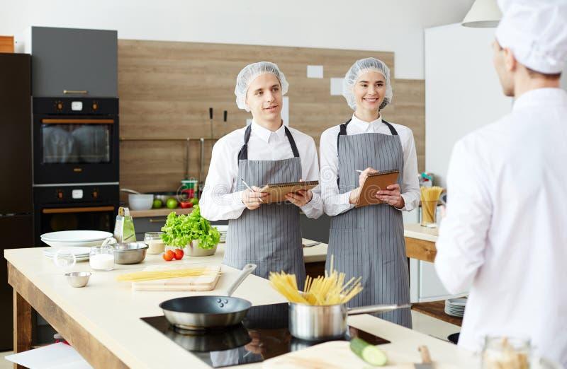 Kokende studenten die aan chef-kok luisteren stock fotografie