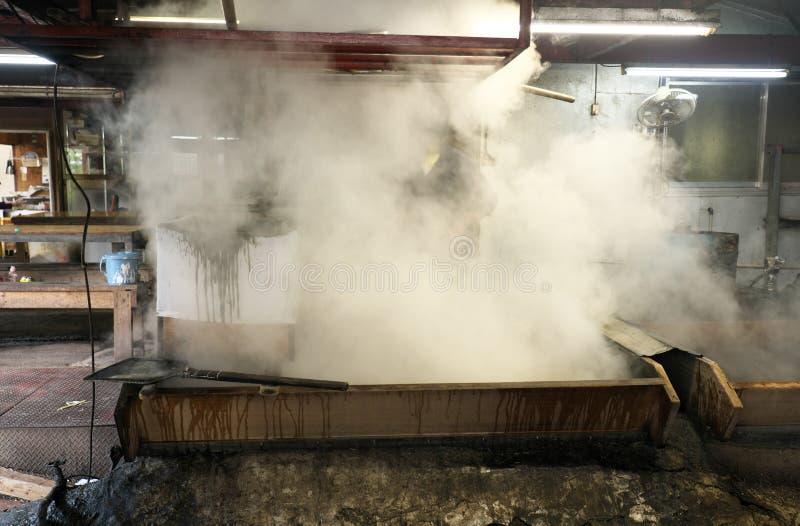 Kokende suikerrietstroop in een pan om bruine suiker in Amami Oshima, Kagoshima, Japan te maken royalty-vrije stock foto's