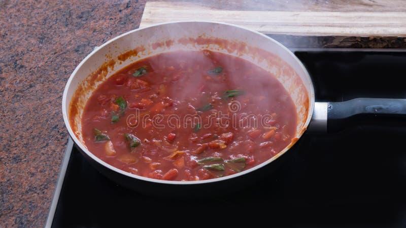 Kokende tomatensaus voor deegwaren stock foto
