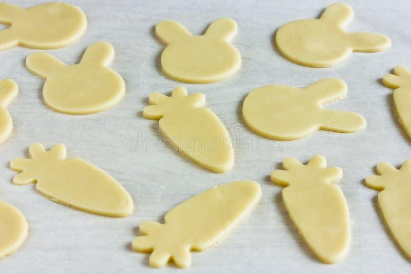 Kokende traditionele koekjes gevormde konijntjes en wortelen voor Pasen stock foto