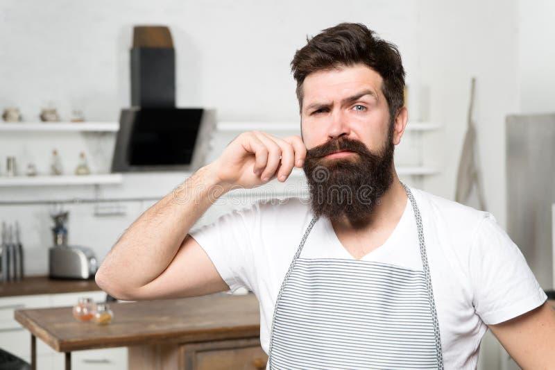 Kokende voedsel van de Hipster het gebaarde mannelijke chef-kok in keuken Keuken voor echte mensen Thuis kokend smakelijk voedsel stock fotografie