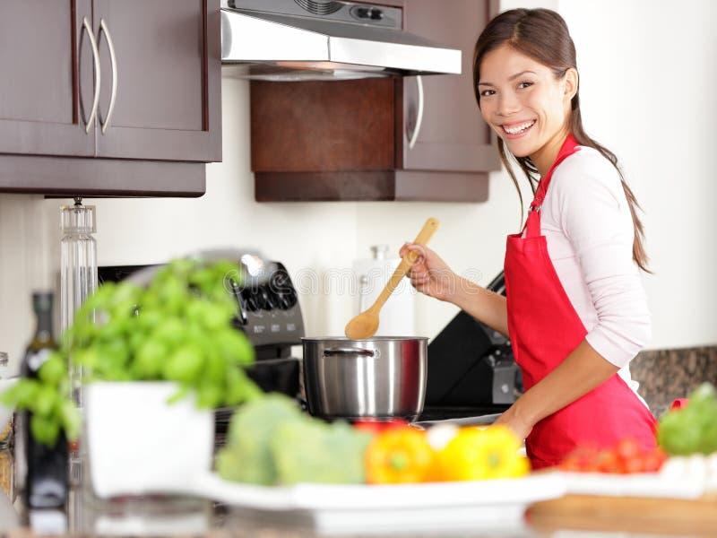 Kokende vrouw in keuken stock foto