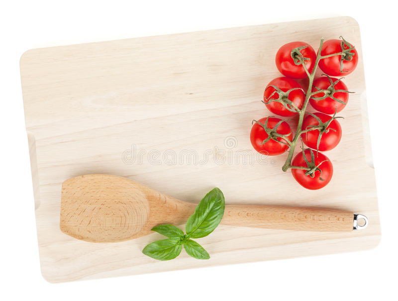 Kokende werktuig en tomaat met basilicum over scherpe raad royalty-vrije stock foto's