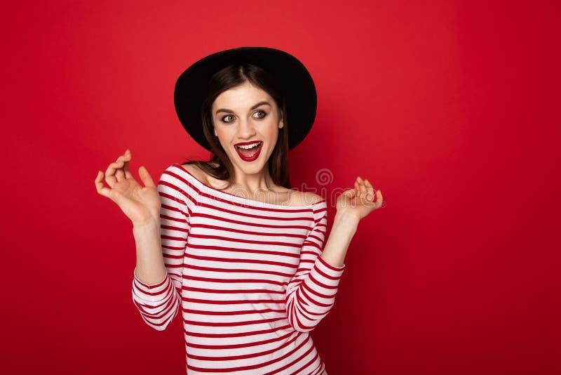 Koket meisje in gestreepte blouse en zwarte hoed royalty-vrije stock fotografie