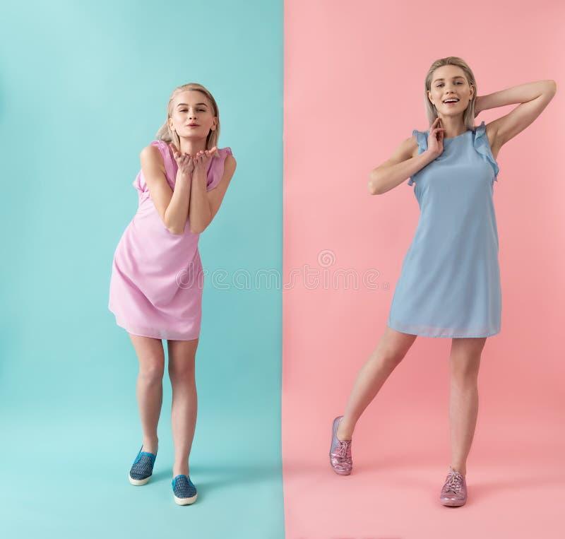 Kokette vrouwen die in kleurrijke kleding stellen stock fotografie