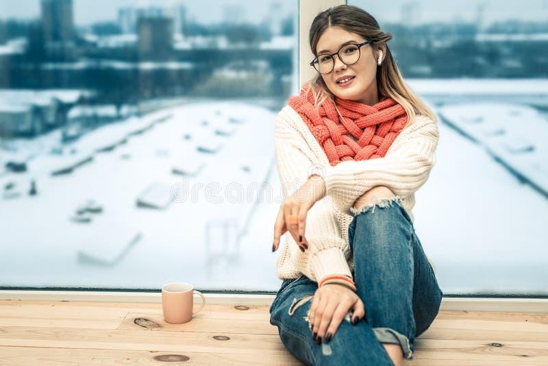Kokettes ruhiges Mädchen, das auf Fenster sich lehnt und Winterstraße auf Hintergrund hat stockfoto