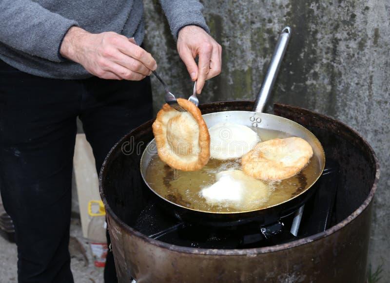 Kokhanden tijdens voorbereiding van fritters stock foto