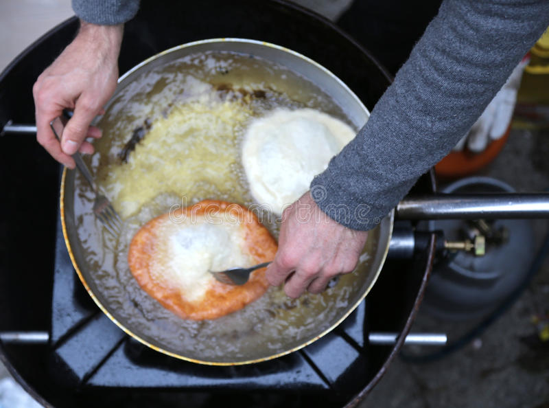 Kokhanden tijdens voorbereiding van fritters in hete olie royalty-vrije stock foto's