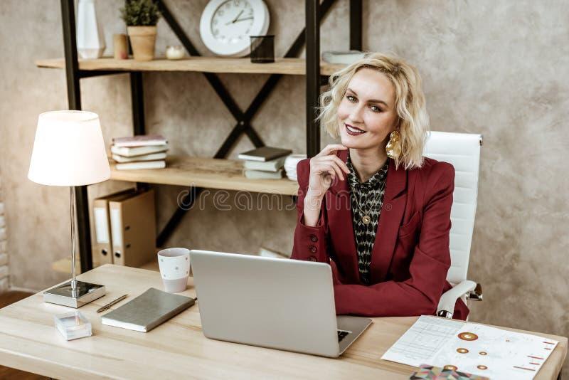 Kokieteryjny blondynki kobiety obsiadanie przy biurkiem przed laptopem obrazy stock